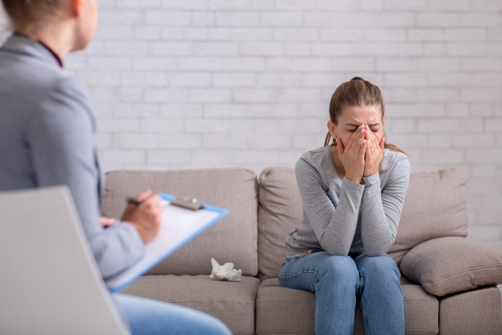 young woman with depression on counseling session with therapist at clinic