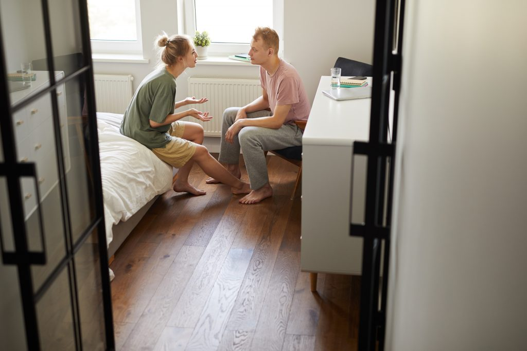 young couple discussing problem while sitting opposite one another in bedroom